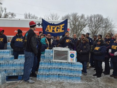 With Flint's water supply in crisis, labor unions have jumped in to help. Here, the American Federation of Government Employees National President J. David Cox, Sr. speaks to volunteers before distributing water to community members.