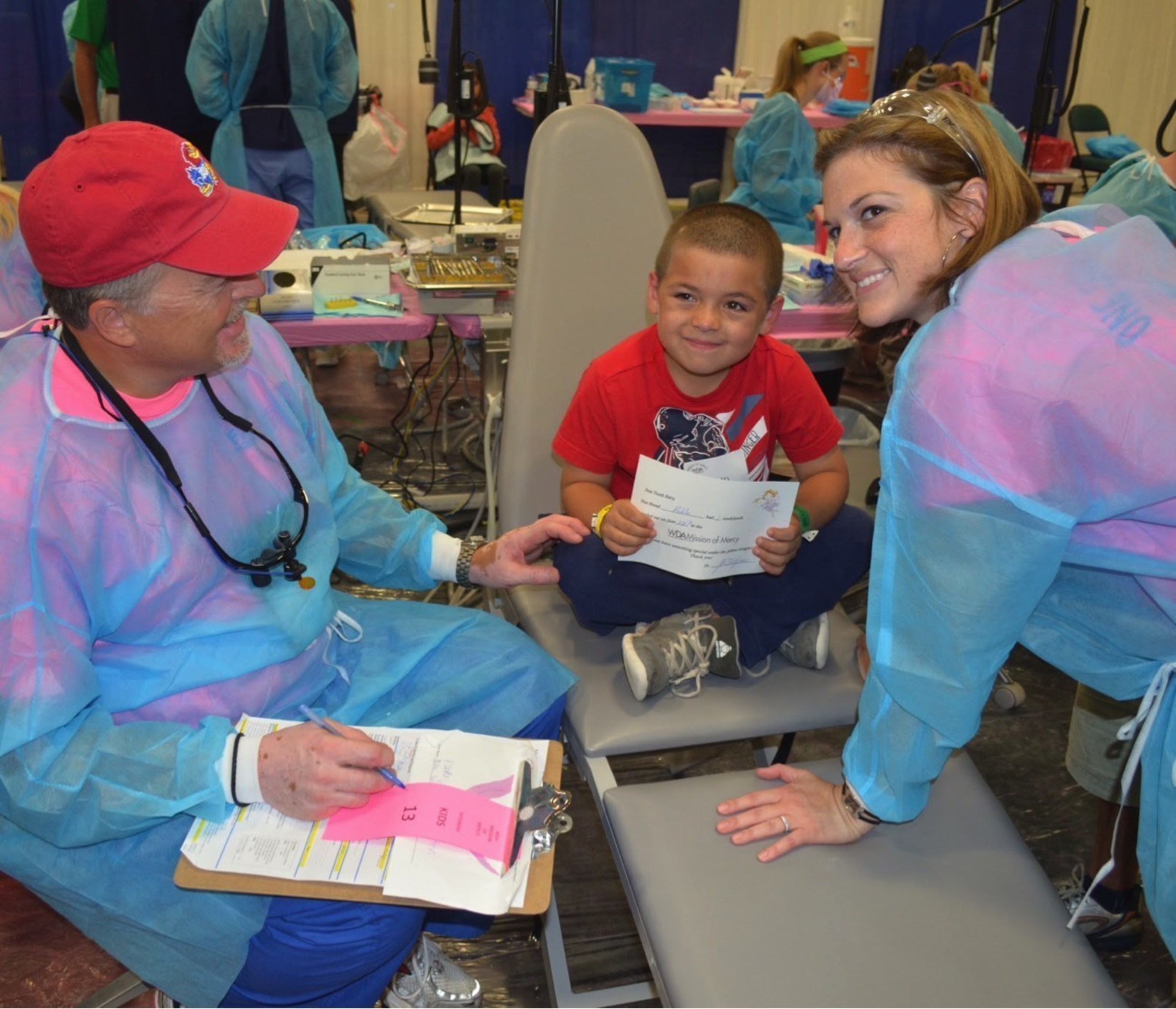 A smiling patient receives oral health care from volunteers at a Missions of Mercy event.