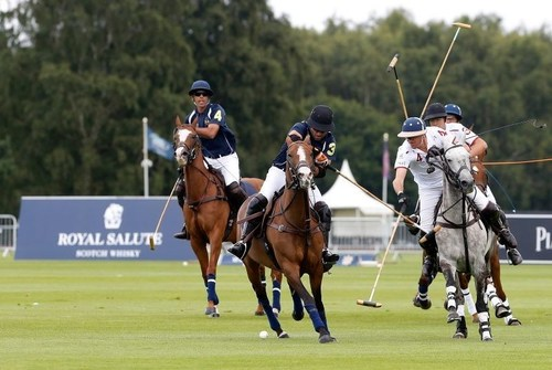 South America (navy) and England fight for the ball during The Royal Salute Coronation Cup at Guards Polo Club ...
