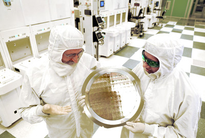 An alliance led by IBM Research has produced the semiconductor industry's first 7nm (nanometer) node test chips with functional transistors. The breakthrough, accomplished at SUNY Polytechnic Institute's Colleges of Nanoscale Science and Engineering (SUNY Poly CNSE), could result in the ability to place more than 20 billion tiny switches -- transistors -- on the fingernail-sized chips that power everything from smartphones to spacecraft. Dr. Michael Liehr (left) of SUNY Poly CNSE and Bala Haran (right) of IBM Research inspect a wafer comprised of 7nm (nanometer) node test chips in a clean room in Albany, NY.
