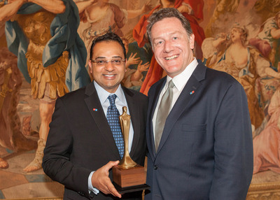 From Driver to Award-Winning Franchisee: Ammar Jali, who started as a delivery driver in 1991 and now owns 25 Domino's Pizza stores throughout Pennsylvania and New York, accepts National Accolade from Domino's CEO Patrick Doyle.  (PRNewsFoto/Domino's Pizza)