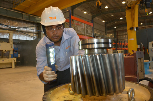 Timken associate Subinoy Das conducts a visual inspection of a bevel pinion at the new Timken industrial ...