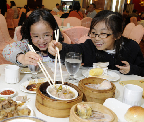 Beracah Lam (right) and Jodi Ho (left) celebrate winning top honors in the 25th Annual Ezra Jack Keats Bookmaking Competition at the restaurant in Brooklyn's Chinatown that inspired their book-Let's Go For Dim Sum. Beracah and Jodi, third graders at P.S. 229, were among the four city-wide winners recognized by the Ezra Jack Keats Foundation in partnership with the NYC Department of Education. The competition was named after the late beloved children's picture book author and illustrator Ezra Jack Keats.  (PRNewsFoto/Ezra Jack Keats  ...