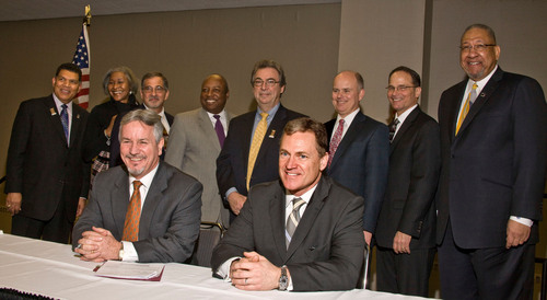 Board members of the Detroit Regional Convention Facility (DRCFA) and the Executive Committee of the North American International Auto Show (NAIAS) are all smiles as they stand behind Cobo Center General Manager Thom Connors (seated, left) and NAIAS Executive Director Rod Alberts (seated, right) after the signing of the agreement. Standing, left to right are: Larry Alexander, DRCFA board chair; Juliette Okotie-Eboh, DRCFA vice-chair: Joe Abdoo, DRCFA secretary; Waymon Guillebeaux, DRCFA project manager; Mike Carroll, DRCFA treasurer; Bob ...