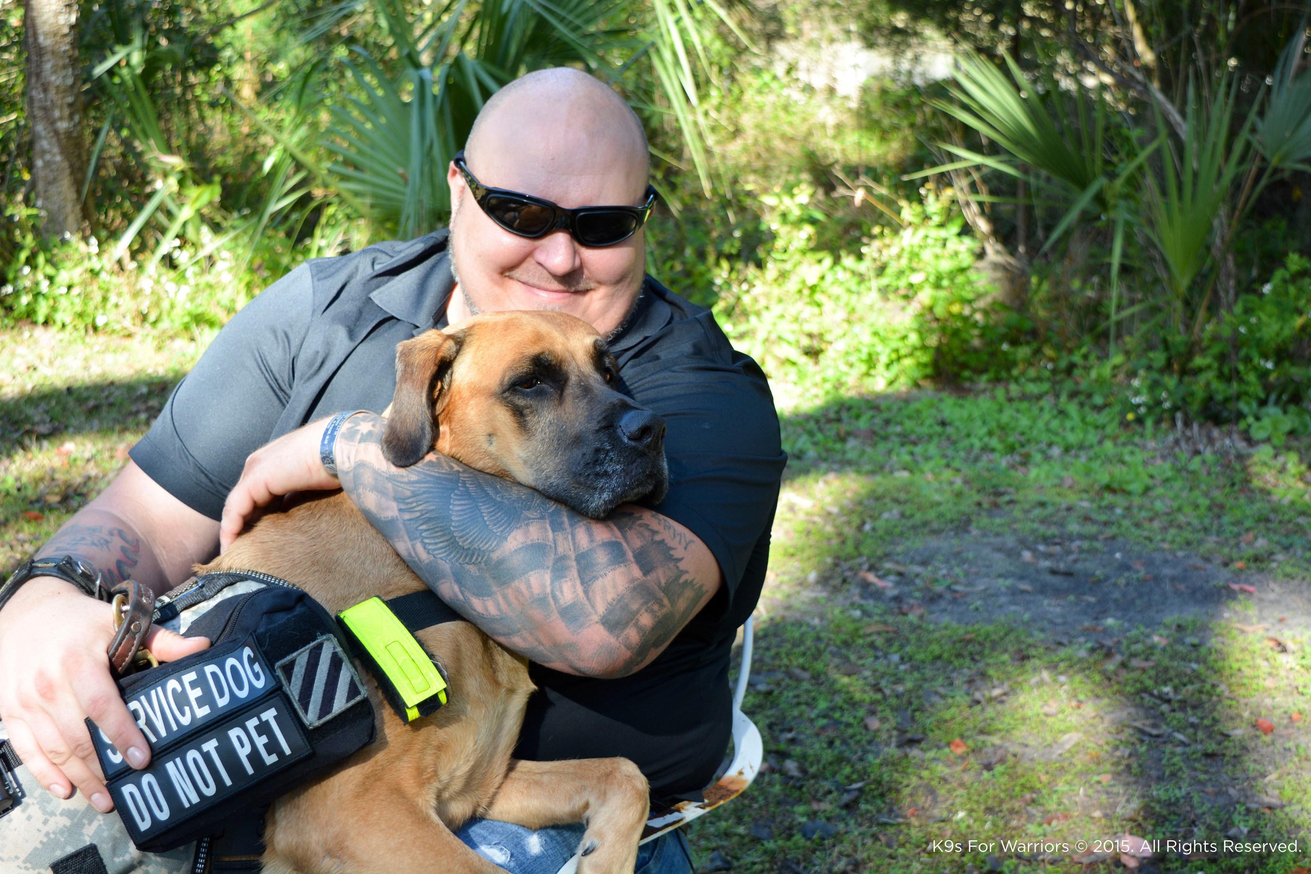 Sergeant First Class U.S. Army (Ret.) Joe Swoboda embraces his service dog Lily.