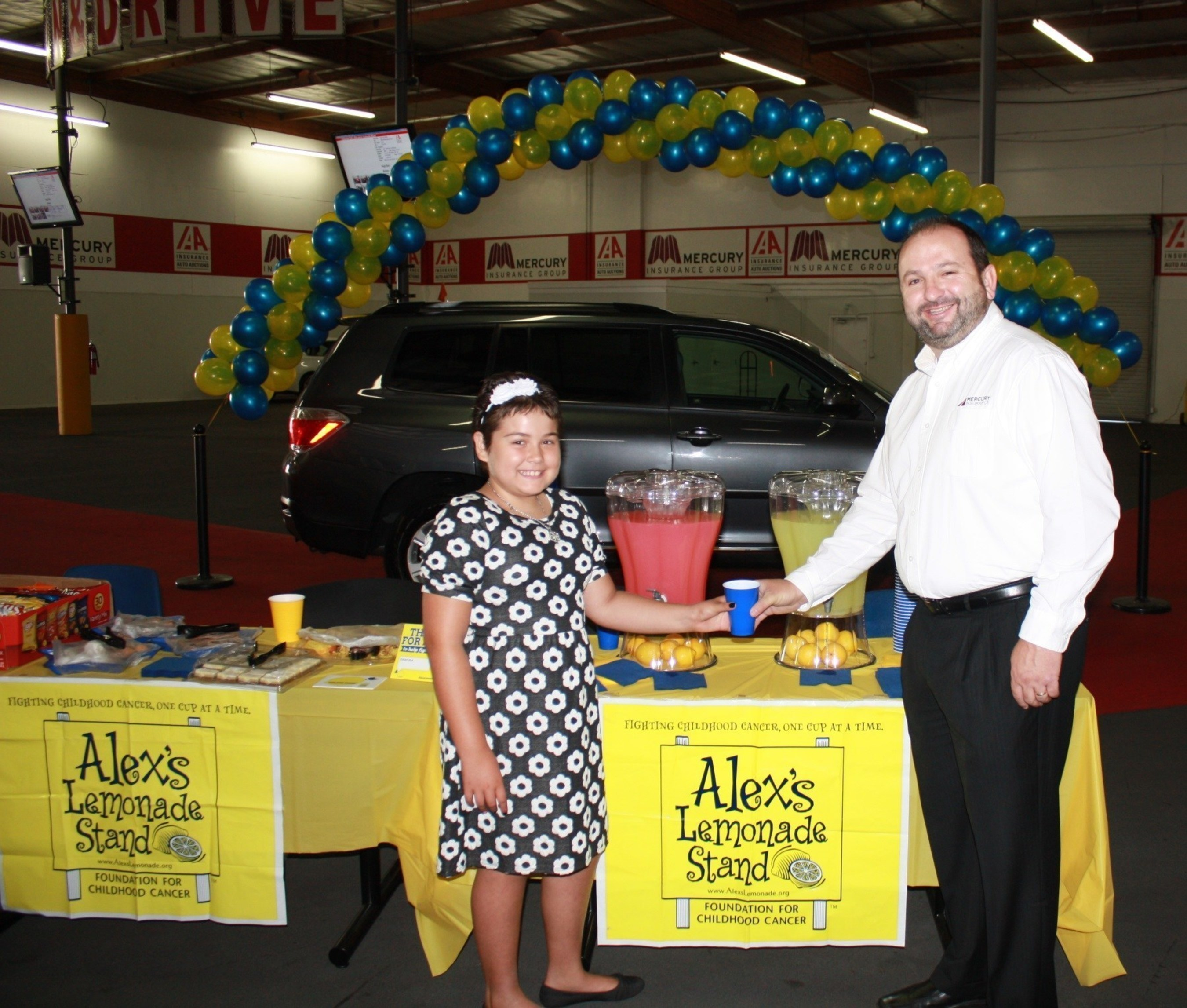 Alex's Lemonade Stand Foundation Hero Karah Casas serves lemonade to Mercury's Jim Bohn at vehicle auction that helped raise $14,700 for childhood cancer research.