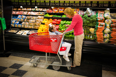 "Caroline in ""Caroline's Cart,"" grocery shopping with her mom, Drew Ann Long, inventor of the first shopping cart designed for children with special needs, that allows them to participate in the family shopping experience.  (PRNewsFoto/Caroline's Cart)"