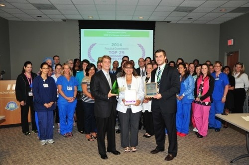 Robert C. Garrett, president and chief executive officer of the Hackensack University Health Network; Bonnie Eskenazi-Melendez, managing director, The Deirdre Imus Environmental Health Center; Kyle Tafuri, sustainability coordinator, The Deirdre Imus Environmental Health Center; and members of HackensackUMC's Green Team receive the 2014 Environmental Excellence Award from Practice Greenhealth's highest honor, earning recognition as one of the top 25 green hospitals in the country. (PRNewsFoto/HackensackUMC)