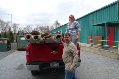 """Sue Matthew, project manager at Sands Bethlehem, a casino and entertainment destination, loads carpet for Luciano """"Lucky"""" Rios, of Metro Design, in Bethlehem, Pa., on Friday, March 18, 2016. Sands Bethlehem sent 17 rolls of unused carpet, totaling more than 18,000 square feet, to Metro Designs to cut into 11 rugs, which will be donated to local non-profits."""