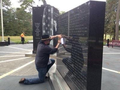 A warrior uses a pencil and paper to create a keepsake at the Fallen Warriors Memorial in Houston.