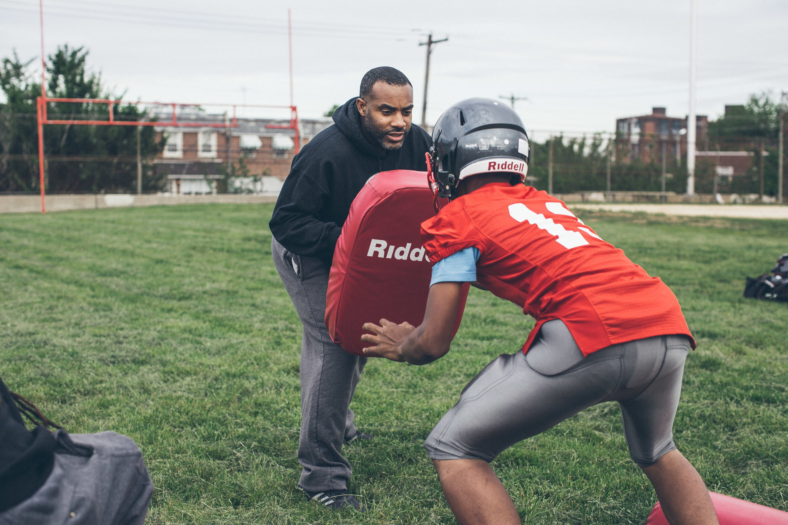 Juniata Thundercats coach and co-founder Lee Taggart teaches proper blocking technique as his players try out new equipment donated to the program as part of Riddell's Smarter Football program.