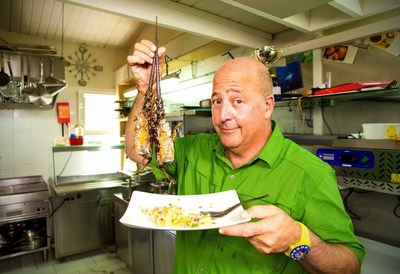 Host Andrew Zimmern holds up his freshly caught Caribbean rock lobster in Guadeloupe