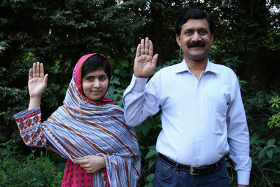 Malala Yousafzai and her father Ziauddin raise their hands to support girls' education.  (PRNewsFoto/Plan International)