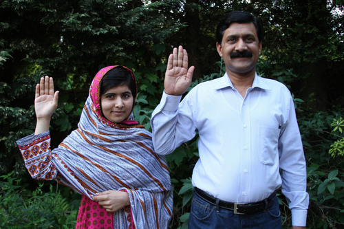 Malala Yousafzai and her father Ziauddin raise their hands to support girls' education.  (PRNewsFoto/Plan ...