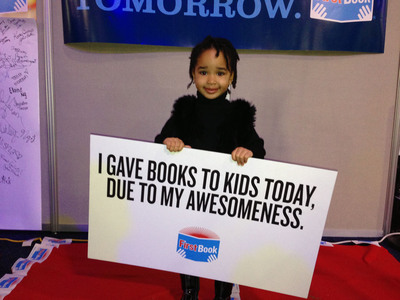 One of First Book's smallest volunteers at today's National Day of Service event on the National Mall, part of the inaugural celebration. Thousands of volunteers packed brand-new books into bags for DC-area children in need and decorated bookplates with personal messages.  (PRNewsFoto/First Book)