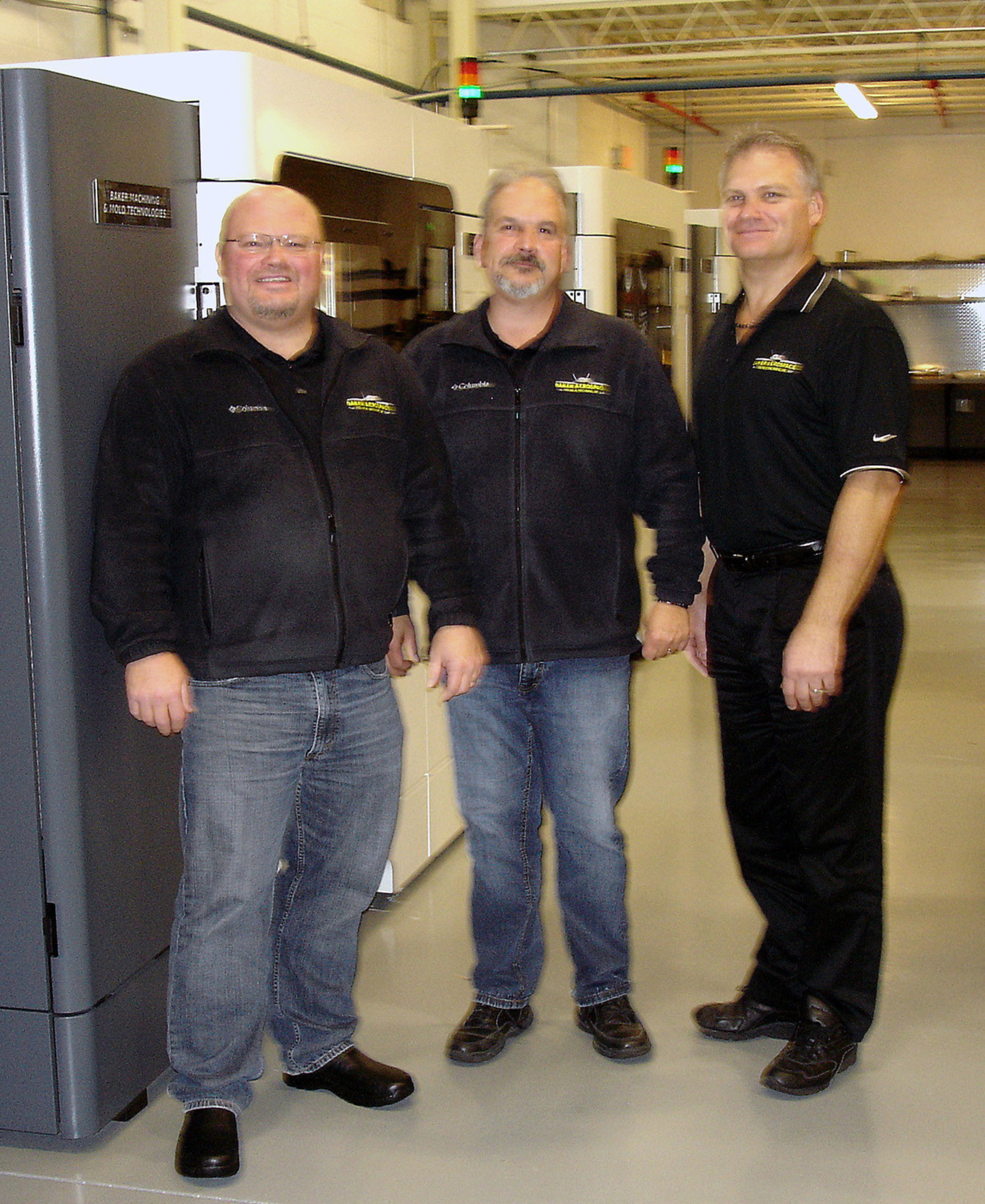 Baker Aerospace founders Scott (left) and Kevin Baker (right) flank new additive & molding tooling director Mike Misener in the company's 3D printing lab.