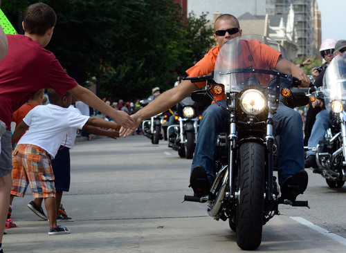 One of nearly 7,000 riders in the Harley-Davidson 110th Anniversary parade interacts with young fans lining the streets of Milwaukee. While tens of thousands of local residents cheered, riders rode nearly five miles through the city.    (PRNewsFoto/Harley-Davidson Motor Company/Mike Fitch)