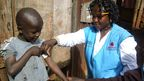 Community Health worker in Kibera area of Nairobi, measuring nutrition grade for child