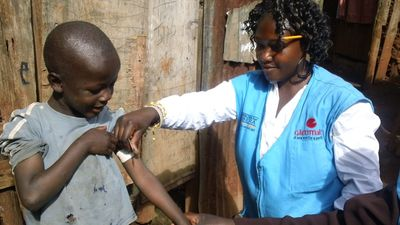 Community Health worker in Kibera area of Nairobi, measuring nutrition grade for child