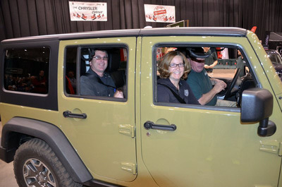 "Sweepstakes winner Cheryl Powers and husband Shawn Powers (back seat) checked out a Jeep(R) Wrangler Unlimited at the Camp Jeep ride and drive and test drove vehicles at the ""Chrysler Group Drive"" while visiting the Cleveland Auto Show.  (PRNewsFoto/Chrysler Group LLC)"
