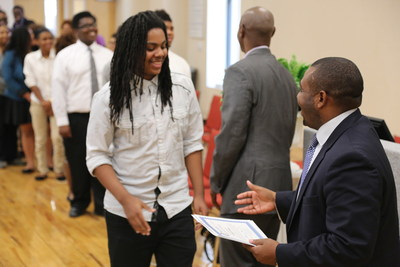 """Student Trenton Rooks accepts his certificate of completion of the """"Earn and Learn"""" summer training program in Memphis. The program helped young adults learn information technology skills. Making the presentation is Kevin Woods, executive director of the Workforce Investment Network of Memphis."""