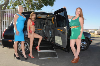 Bunny Ranch prostitutes pose next to the brothel's ADA compliant British taxi used for transporting their physically challenged clients.