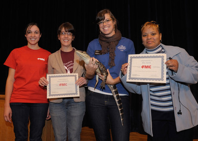 Pictured from left, FMC fungal researcher Kimberly Reed presents certificates to teacher Stacey Dello Bruno from Thomas Mifflin Elementary School and teacher Alva Austin from Francis Pastorius Elementary School.  Jill Sybesma, adult programs coordinator at the Academy of Natural Sciences at Drexel University, congratulates the teachers before kicking off a live animal show. Teachers Kathleen Geist from Green Woods Charter School and Frances Wilson from Houston Elementary School also received gift certificates at the second FMC STEM Career Day.  (PRNewsFoto/FMC Corporation)