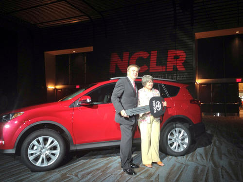 Toyota Senior Vice President Bob Carter stands with Amparo Nunez of Tampa, who won a RAV4 during the 2013 National Council of La Raza annual conference.  (PRNewsFoto/Toyota)