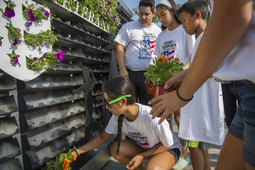"""Student volunteers pay tribute to Post 9/11 Military Veterans by participating in the Code of Support Foundation's """"Living Wall of Honor"""" service project at the World War II Memorial in Washington, D.C. on Sun., Aug.10. The Living Wall of Honor is comprised of more than 1000 plants and will be on exhibit at the Women In Military Service For America Memorial at the main gate to Arlington National Cemetery where it is expected to remain through September 11, 2014. Photo/Rodney Lamkey (PRNewsFoto/The Code of Support Foundation)"""