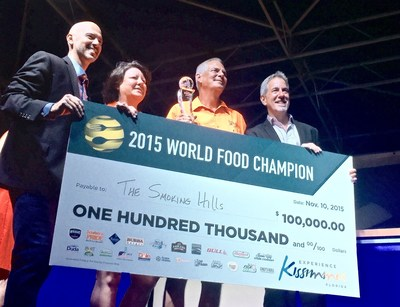 "Cheryl and Loren Hill, of ""The Smoking Hills"" from Overland Park, Kansas, hold their $100,000 presentation check from World Food Championships. Also pictured is Mike McCloud, CEO (far right) and Larry Oliphant, Vice President (far right), both of World Food Championships."