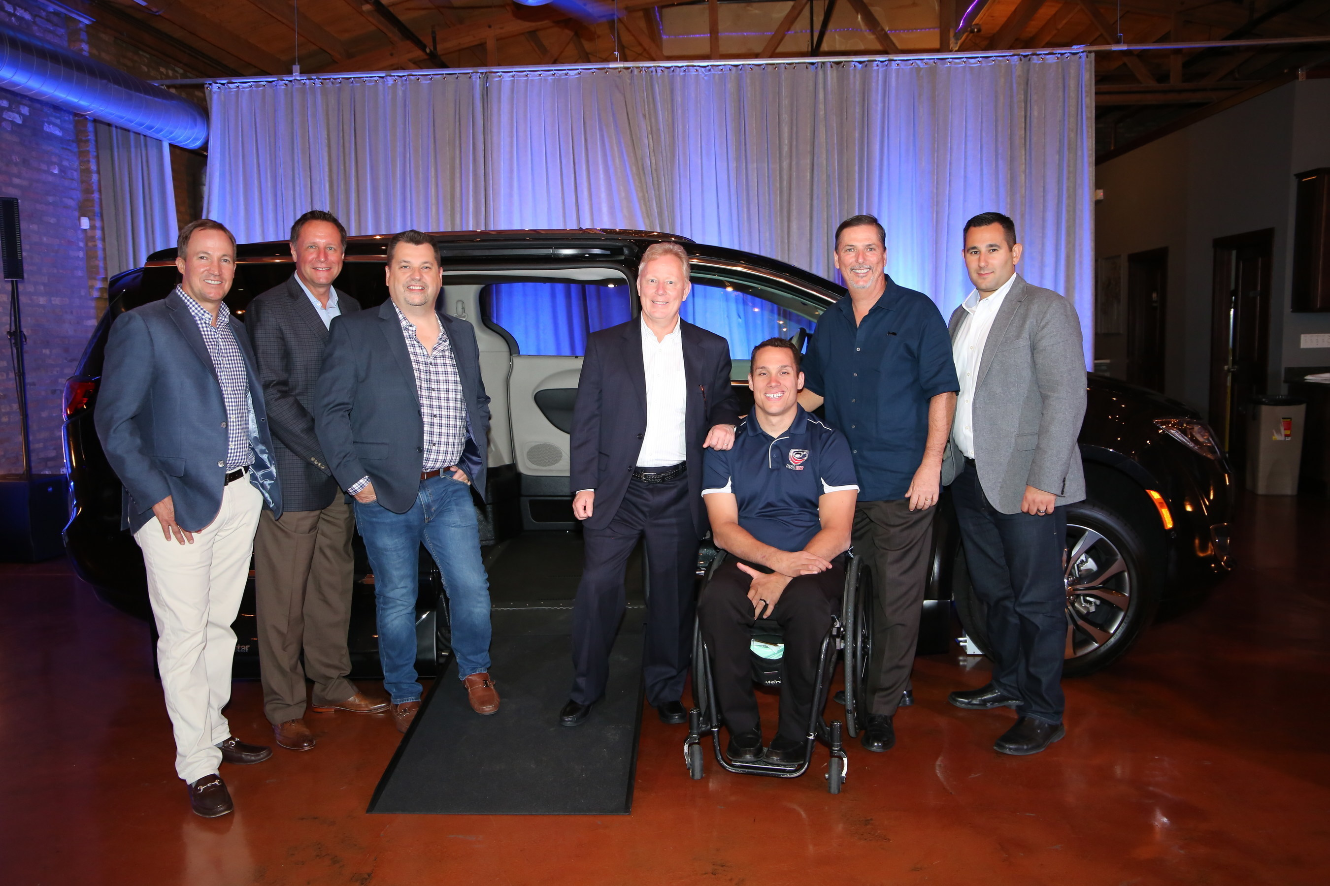 VMI introduces industry's first Chrysler Pacifica side-entry conversion to the Dealer Council Executive Committee in Chicago, Il.  Shown here at the event are from left, Doug Eaton, VMI CEO, Michael Ring, FCA, Steve Crandell, VMI COO, Len Norton, Chairman of VMI Dealer Council, Joe Delgrave, Team USA, Paralympian and new VMI spokesperson, Tim Barone, VMI CFO, and Matt Huber, FCA.