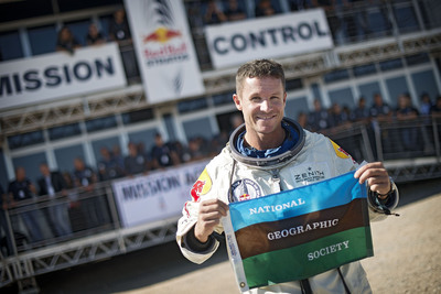 Felix Baumgartner celebrates by holding the National Geographic Society flag -- joining explorers like James Cameron and Dr. Bob Ballard in marking a groundbreaking achievement in exploring our world - which will be chronicled in full with exclusive behind-the-scenes detail in a National Geographic Channel special airing in November.  (PRNewsFoto/National Geographic Channels)