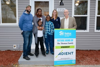 Adient, the world's largest global automotive seating supplier, presented the keys to an Ypsilanti Township home to Christina Thomas and her family (center) this week . Russ Burgei, (far right) vice president of engineering for Adient and the company's Habitat for Humanity project leader, and representatives from Habitat of Huron Valley took part in the event.
