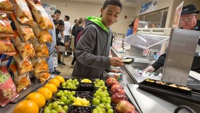 Students in lunch line are offered foods and drinks that meet strong nutrition standards. Studies have found that the location of fruits and vegetables in school lunch lines can significantly increase consumption of those healthier foods.