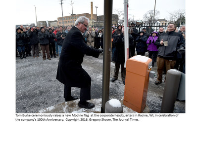Tom Burke ceremoniously raises a new Modine flag at the corporate headquarters in Racine, WI, in celebration of the company's 100th Anniversary. Copyright 2016, Gregory Shaver, The Journal Times.