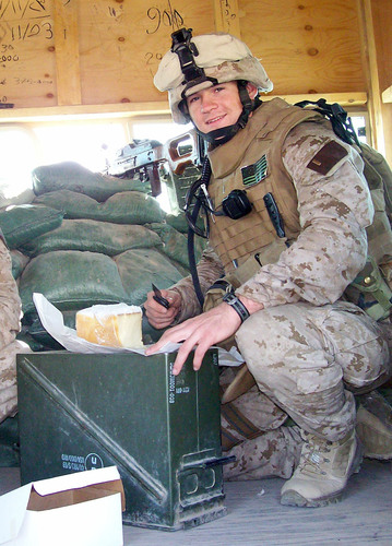 Platoon Commander Gary Laughlin pounds a cake sent from Philadelphia while inspecting a post in Fallujah, Iraq.  ...