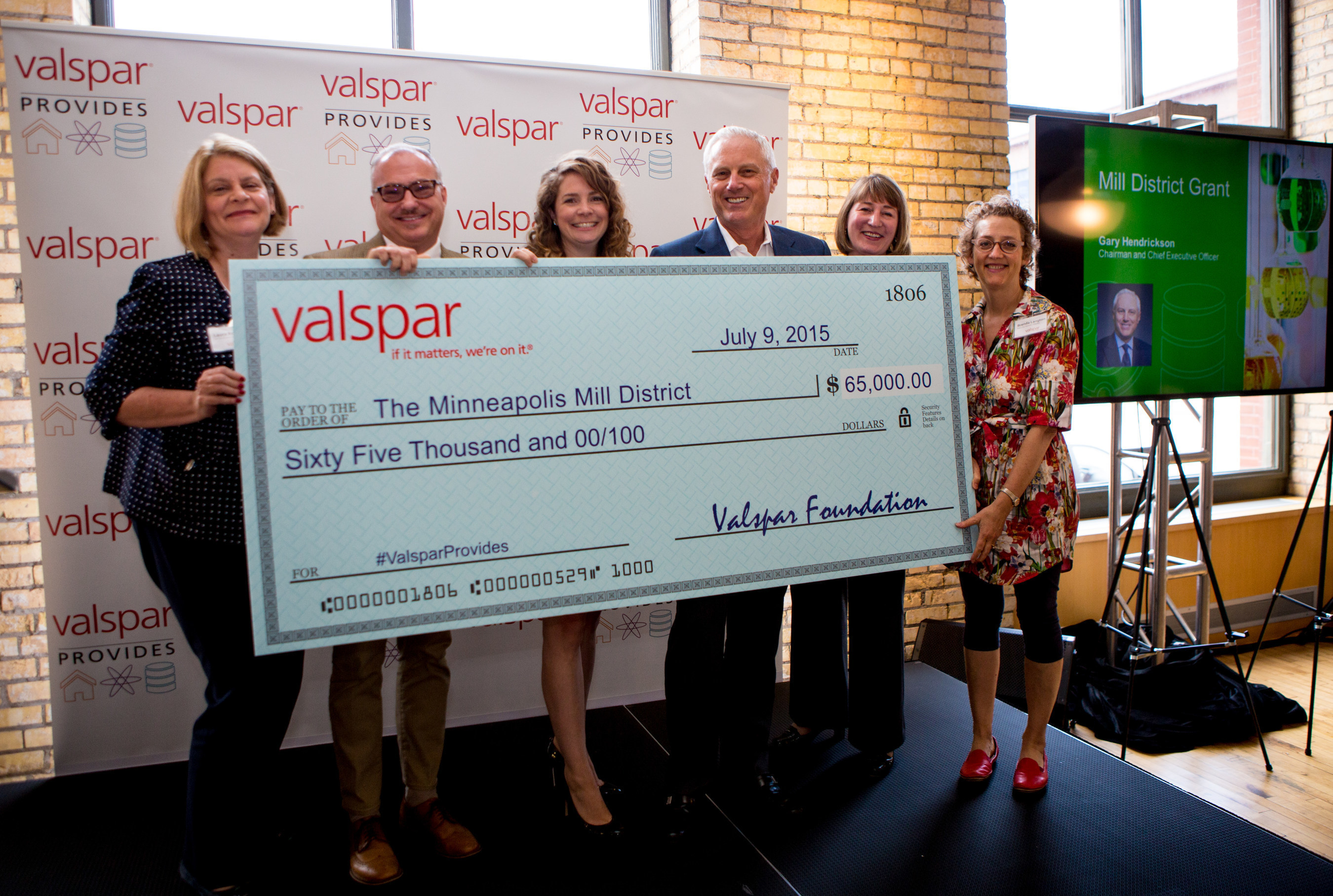 """To commemorate the return of Valspar Corporation's headquarters to the historic Mill District area in Minneapolis, the Valspar Foundation announced $65,000 in grants to five non-profit organizations. Pictured with Valspar Chairman and CEO Gary Hendrickson (third from right) are (l-r) Laura Roller of Mill City Museum, Jeff Rathermel of Minnesota Center for Book Arts, Emily Dehn of The Guthrie Theater, Gary Hendrickson, Valspar, Jennifer Halcrow of MacPhail Center for Music, and Brenda Langton, founder of the Mill City Farmers Market. """"As Minneapolis is Valspar's global headquarters community, we are pleased to support the Mill District neighborhood,"""" said Gary Hendrickson."""
