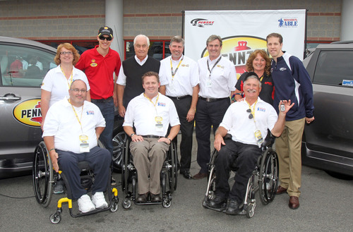 "John Scott and his wife,  Penske Racing driver, Joey Logano, Roger Penske, owner of Penske Racing, Al Kovach, Jr, National Senior Vice President, Paralyzed Veterans of America, Rusty Barron, Vice President of Marketing, Shell Lubricants, Istavan Kapitany, President of Shell Lubricants Americas, Hank Ebert and his wife and Penske Racing driver Brad Keselowski (all from left to right) unveil retrofitted vehicles, donated by Pennzoil through Paralyzed Veterans of America's ""Mission: ABLE"" campaign on Saturday, October 12th, 2013 at ..."
