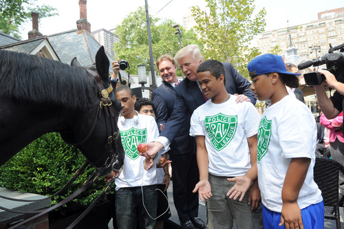 "Donald Trump and Mark Bellissimo, CEO of Equestrian Sport Productions and owner and publisher of Chronicle of the Horse, joined by youth from the Police Athletic League NYC, feed an apple to NYPD Mounted Unit horse Torch, after announcing that the first ever ""Central Park Horse Show Presented by Rolex"" will come to Central Park's Trump Rink from September 18- 21, 2014 during a press conference at Tavern on The Green, Tuesday, July 29, 2014, in New York. (Photo by Diane Bondareff/Invision for Chronicle of the Horse) ..."