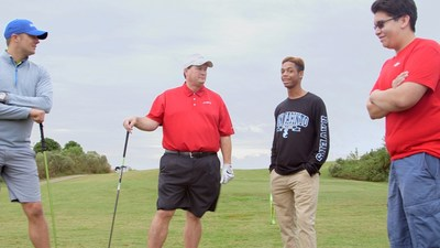Todd Monette, LyondellBaasell and EHCMA Board Chairman, and Tex Woodall, Lee College instrumentation instructor, talk with students during the golf tournament.