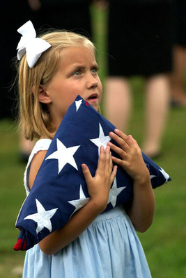 The great-granddaughter of a Veteran cared for by Columbus Hospice of Alabama's program in Georgia holds the U.S. flag at her great-grandfather's burial service.  (PRNewsFoto/National Hospice and Palliative Care Organization)