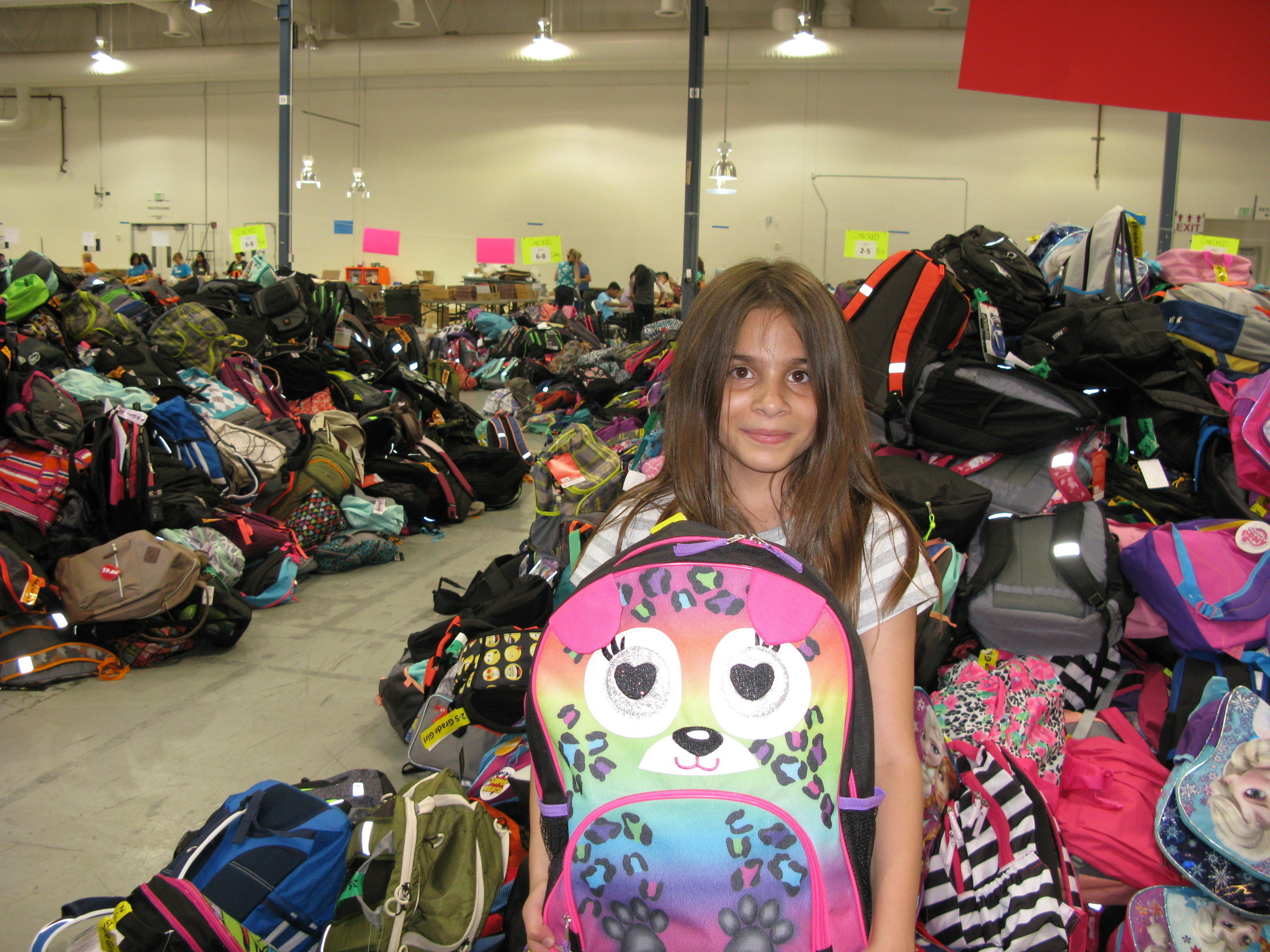 A youth volunteer stands among a sea of backpacks ready for distribution during last year's Back-to-School Drive.