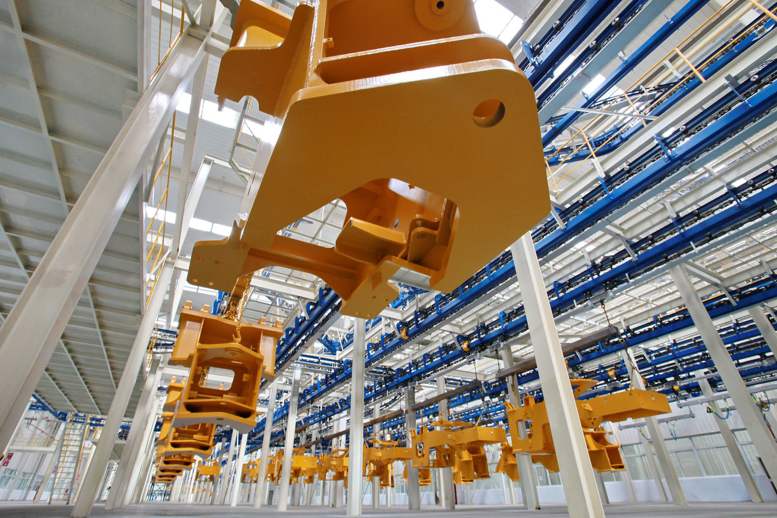 After coating by robots, components of XCMG's products are automatically transported to various assembly ...