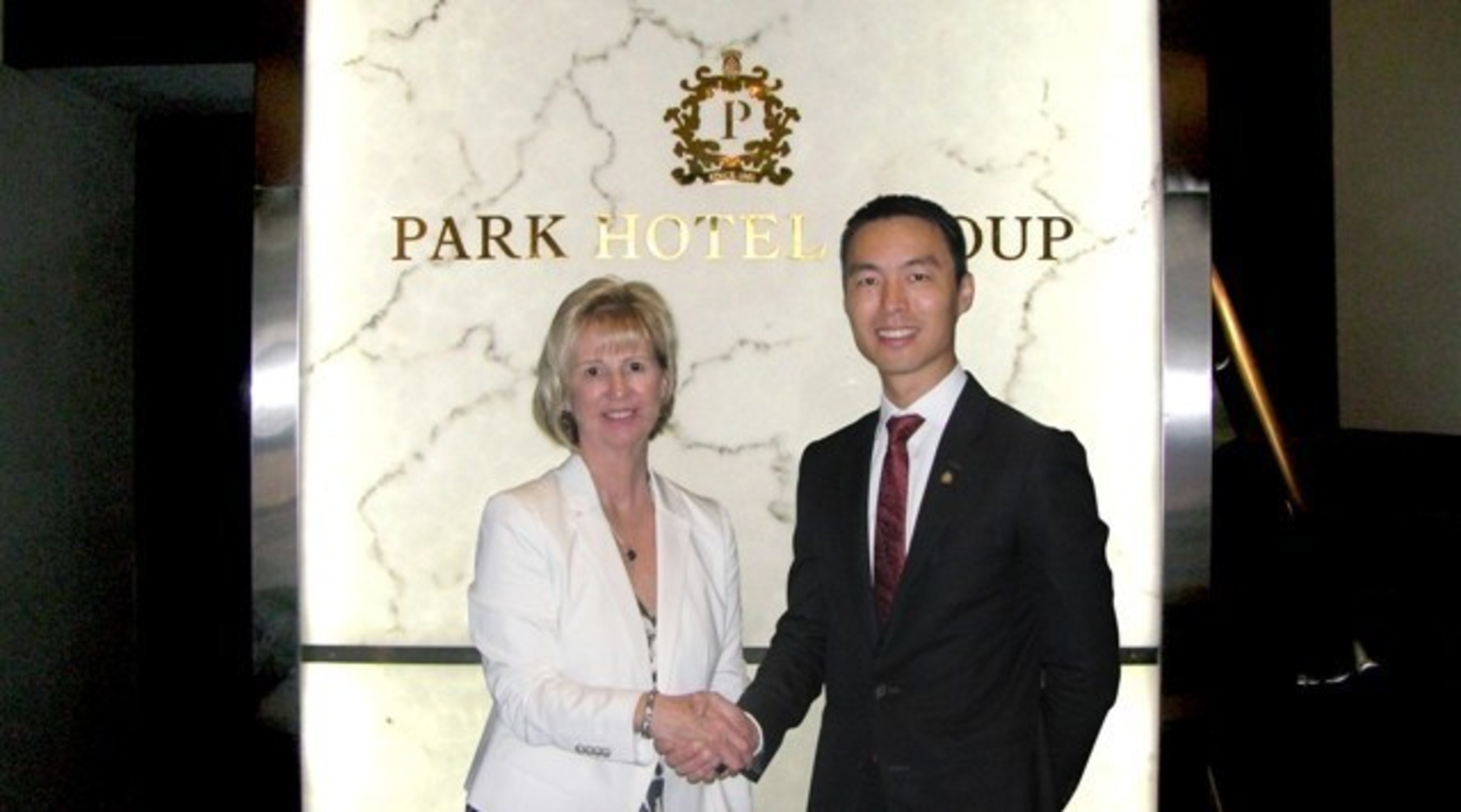 Allen Law, CEO of Park Hotel Group and Jenny Adams, CEO of Discover the World, extending a firm handshake symbolic of a robust partnership to come.