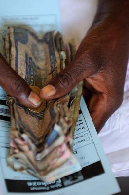 Darcy Kiefel, 2011 CGAP Photo Contest. A client reimburses part of a microfinance loan that she received from Fonkoze in Limbe, Haiti.  (PRNewsFoto/CGAP)
