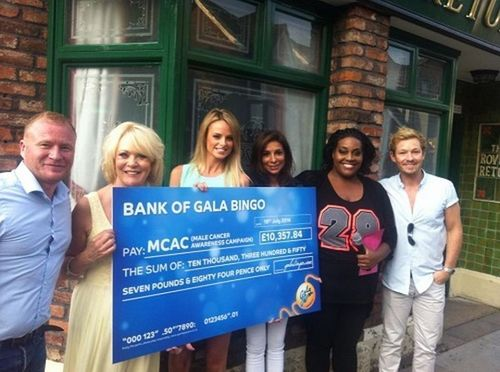MCAC ambassador, Rhian Sugden, accepts a cheque for over £10,000 raised by GalaBingo.com members before the GUINNESS WORLD RECORDS(TM) achievement for the largest set of bingo balls at the Coronation Street Tour location. (PRNewsFoto/Gala Interactive)