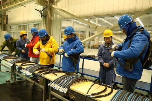 XCMG Apprentices were focused in the competition of installing rubber tube protectors.