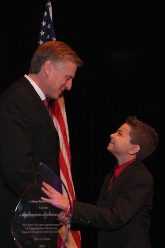 New York Blood Center (NYBC) President and CEO Christopher D. Hillyer, MD, congratulates Rafaello Carone, 12, a  ...