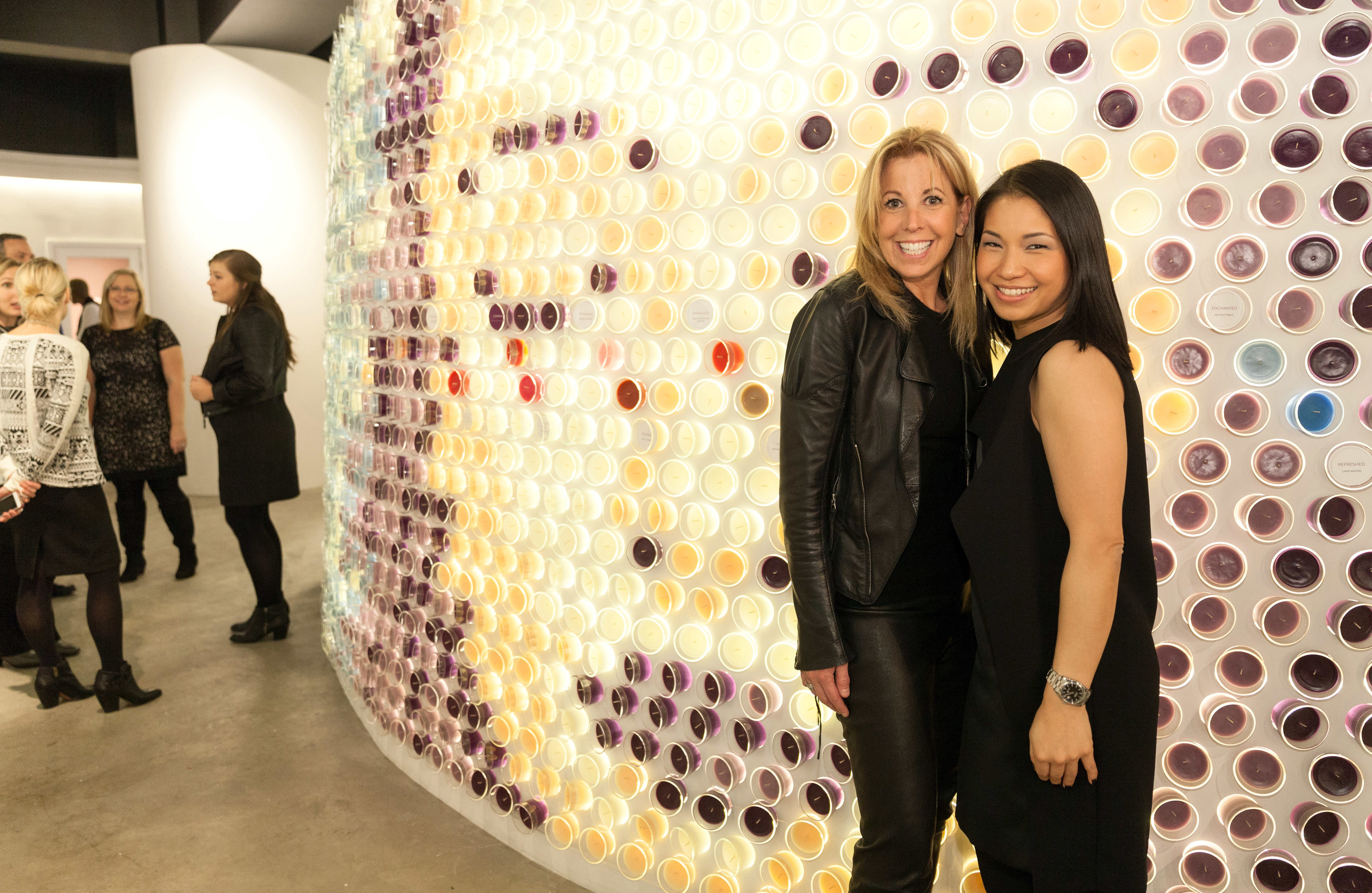 Celebrity fashion designer Pamela Dennis, left, and New York-based designer and architect Stephanie Goto celebrate the grand opening of the Glade(R) Boutique in front of Goto's scent-inspired creation compiled of nearly 1,500 candles in 18 Glade(R) scents Monday, Nov. 17, 2014 in New York.
