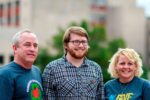 Zack Poe (middle), the first patient in Kentucky to be bridged to transplant with the SynCardia Total Artificial Heart, poses with his father Tony and his mother Laurie outside University of Kentucky Medical Center.  (PRNewsFoto/SynCardia Systems, Inc.)
